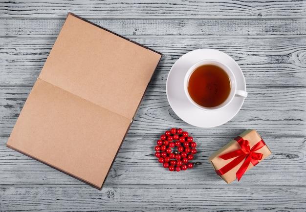 Otwarta książka z pustymi stronami, filiżanką czarnej herbaty, prezentem i czerwonymi koralikami