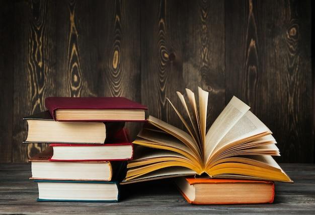 Otwarta książka z żółtymi stronami na drewnianej tło kopii przestrzeni. stary podręcznik. stos książek.