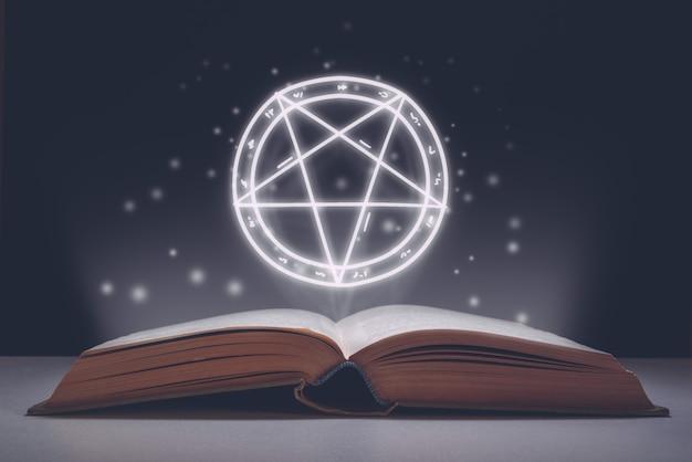 Otwarta księga zaklęć z projekcją gwiaździstego piktogramu jako symbolu zła. święto halloween.