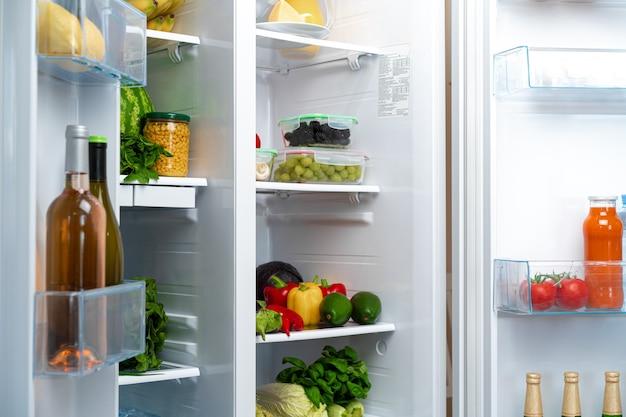 Otwarta lodówka pełna owoców, warzyw i napojów