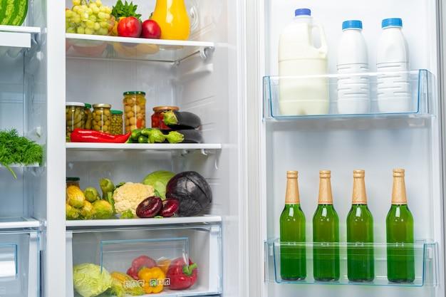 Otwarta lodówka pełna świeżej żywności i napojów