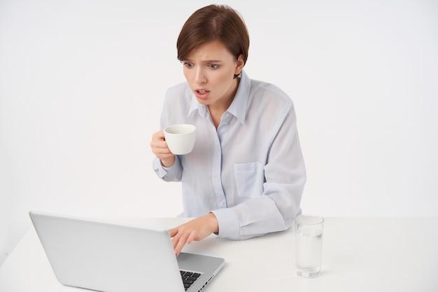 Otwarta, młoda ładna brązowowłosa kobieta z przypadkową fryzurą, trzymająca ceramiczny kubek i patrząc zdumiewająco na ekran laptopa, czytająca nieoczekiwane wiadomości, na białym tle