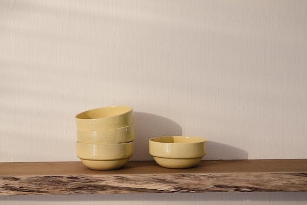Otwarta pływająca drewniana półka ze stosem czterech żółtych ręcznie robionych ceramicznych talerzy wiszących na białej ścianie w nowoczesnym salonie. przytulna, minimalistyczna koncepcja domu.