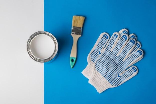 Otwarta puszka białej farby, rękawiczki i pędzelek na niebiesko-białym tle