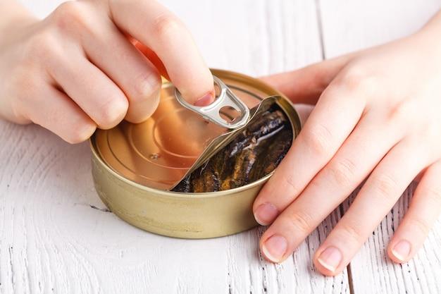 Otwarta puszka ryb z rękami i widelcem na stole