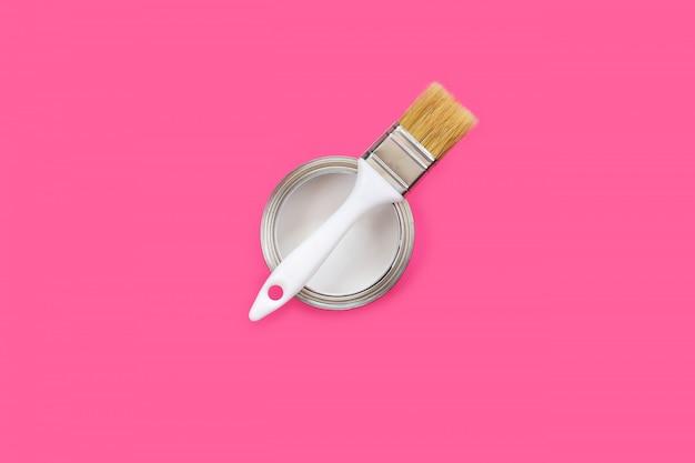 Otwarta puszka z białą farbą i pędzlem na różowym tle.