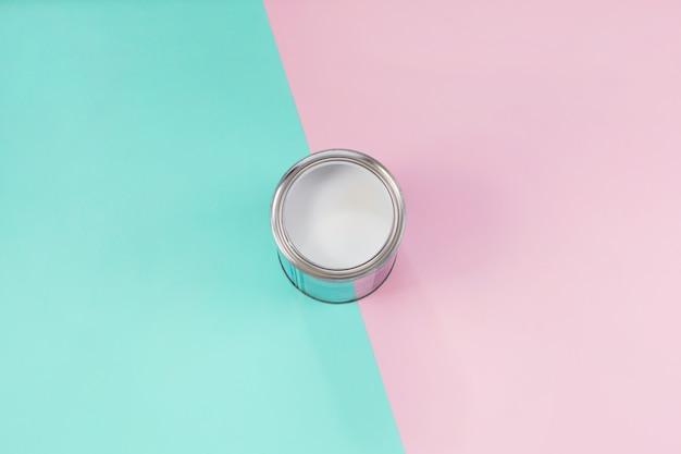 Otwarta puszka z białą farbą na pastelowym tle koloru.