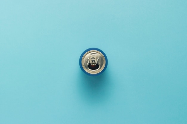 Otwarta puszka z napojem lub pusta na niebieskim tle. minimalizm. pojęcie dnia i nocy, kofeina, napój energetyczny, wakacje. leżał płasko, widok z góry.
