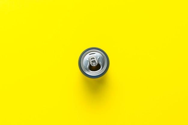 Otwarta puszka z napojem lub pusta na żółtym tle. minimalizm. pojęcie dnia i nocy, kofeina, napój energetyczny, wakacje. leżał płasko, widok z góry.