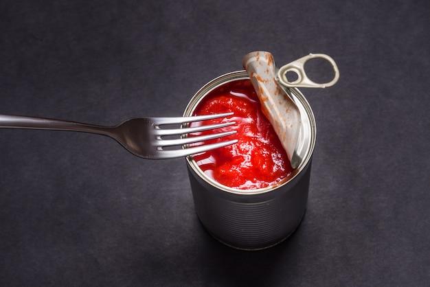 Otwarta puszka z pomidorami w puszkach, na czarnym tle