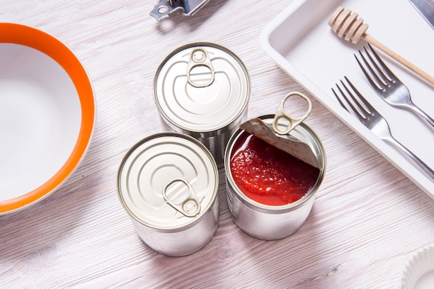Otwarta puszka z pomidorami w puszkach, na drewnianym stole w kuchni