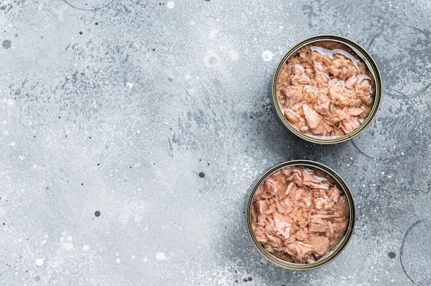 Otwarta puszka z tuńczykiem w puszkach. szare tło. widok z góry. skopiuj miejsce.