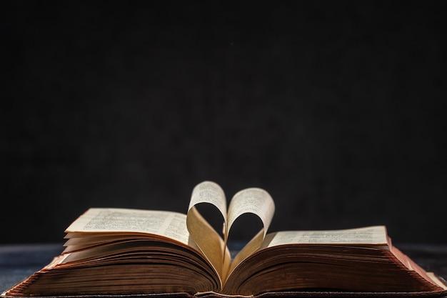 Otwarta stara księga z sercem ułożonym z dwóch stron. otwarte strony tworzą serce symbolem miłości