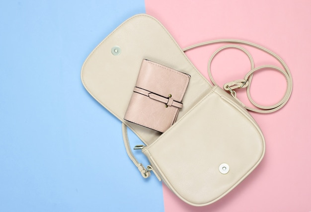 Otwarta stylowa skórzana torebka z torebką na pastelowym tle
