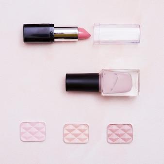 Otwarta szminka; lakier do paznokci butelki i cień do powiek na różowym tle