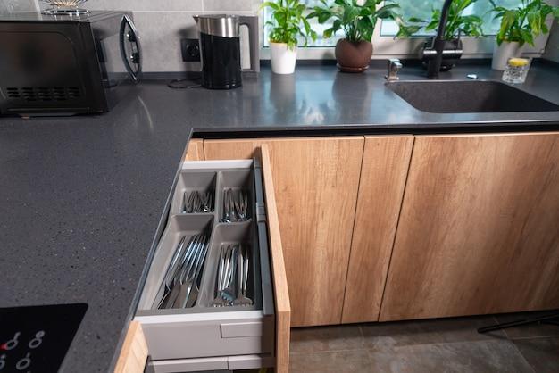 Otwarta szuflada na sztućce w nowoczesnej wyposażonej kuchni z drewnianymi szafkami w domu pokazująca starannie ułożone noże, widelce i łyżki w poszczególnych przegrodach