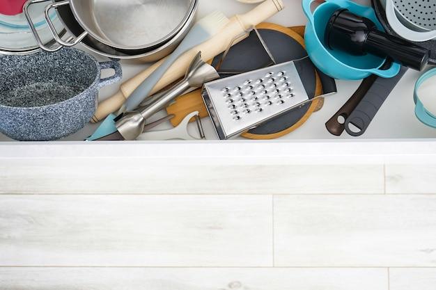 Otwarta szuflada z różnymi naczyniami i sztućcami w kuchni, widok z góry. miejsce na tekst.