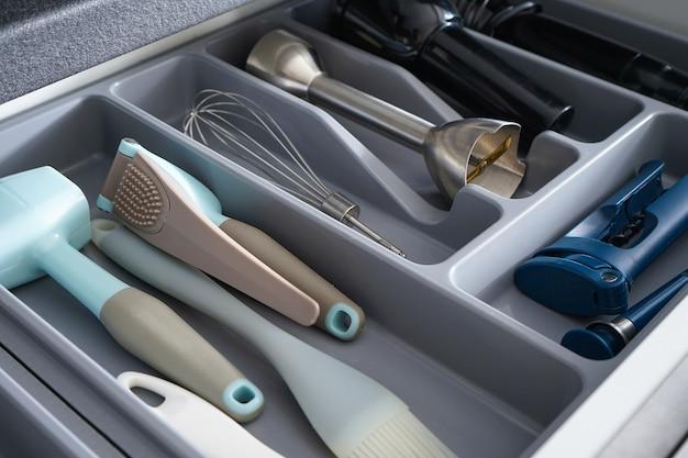 Otwarta szuflada z różnymi naczyniami i sztućcami w kuchni. zbliżenie.