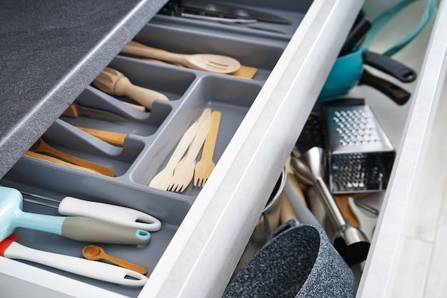 Otwarta szuflada z różnymi naczyniami i sztućcami w kuchni.