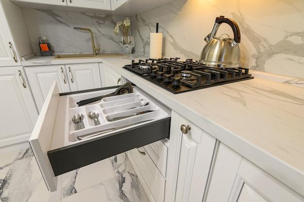 Otwarta szuflada ze sztućcami w nowoczesnej, białej kuchni w klasycznym stylu