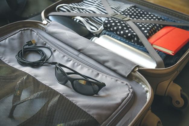 Otwarta walizka podróżna w stylu vintage pełna ubrań