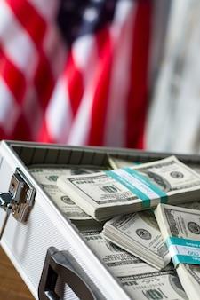 Otwarta walizka z paczkami dolarowymi. gotówka w pobliżu amerykańskiej flagi. wolność i możliwości. bogactwo i chwała.