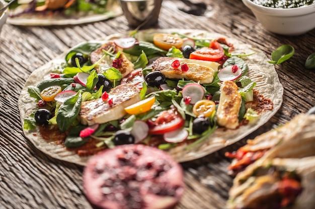 Otwarta wegetariańska tortilla z sałatką, rzodkiewką, pomidorkami cherry, oliwkami, granatem i grillowanym serem haloumi.