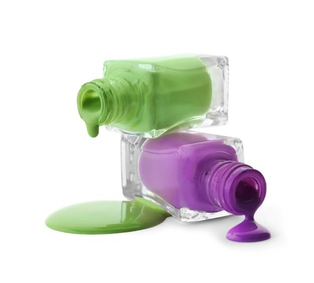 Otwarte butelki z kapiącymi lakierami do paznokci