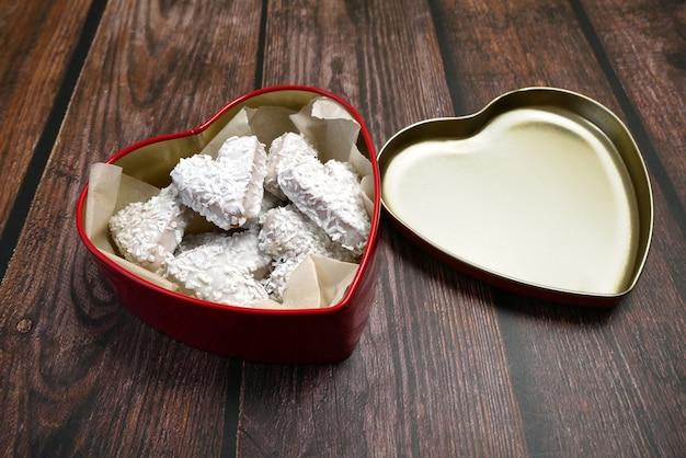 Otwarte czerwone pudełko w kształcie serca i smaczne ciasteczka z kokosem