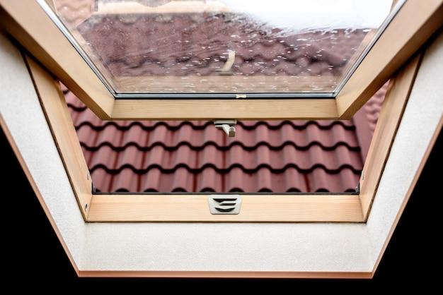 Otwarte drewniane okno na poddaszu z widokiem na ulicę