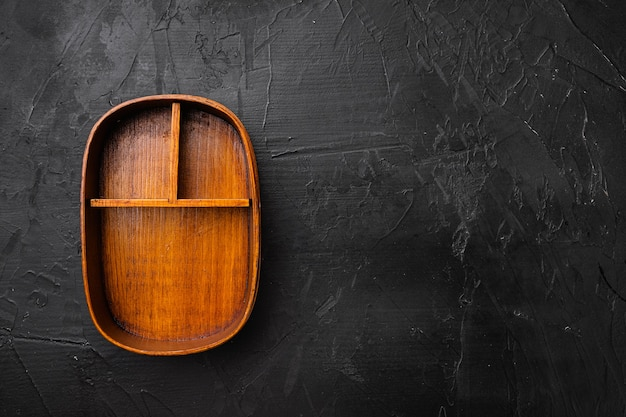 Otwarte drewniane pudełko bento z miejscem na kopię na tekst lub jedzenie z miejscem na kopię na tekst lub jedzenie, widok z góry płasko leżący, na tle czarnego ciemnego kamiennego stołu