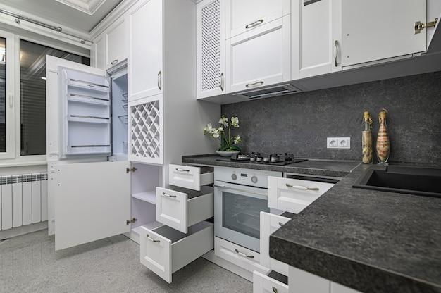 Otwarte drzwi i szuflady mebli w nowoczesnej, czarno-białej, drewnianej kuchni w klasycznym stylu
