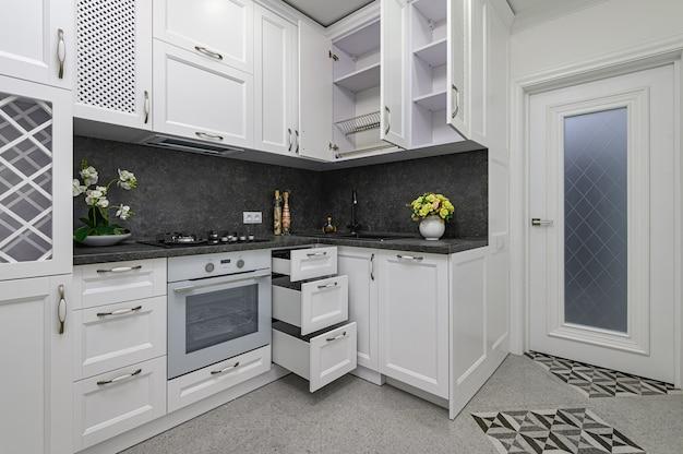 Otwarte drzwi i szuflady otwierają się w nowoczesnej białej kuchni