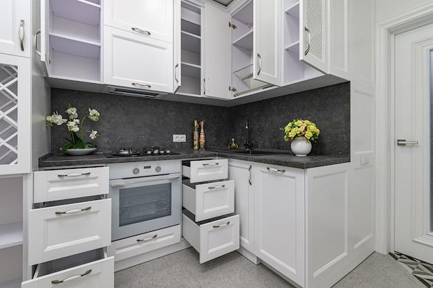 Otwarte drzwi i szuflady w nowoczesnej, czarno-białej, drewnianej kuchni w klasycznym stylu