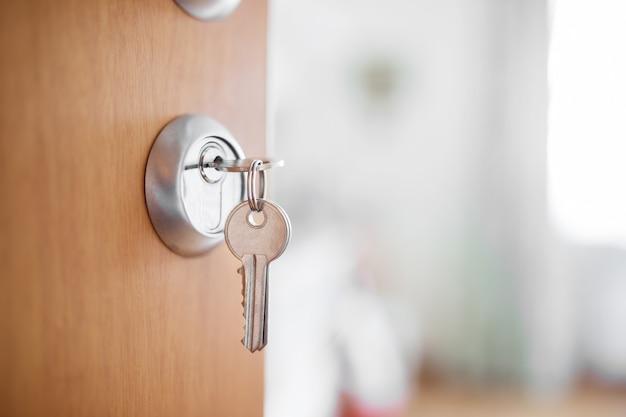 Otwarte drzwi z kluczami, klucz w dziurce od klucza, w tle sypialnia.