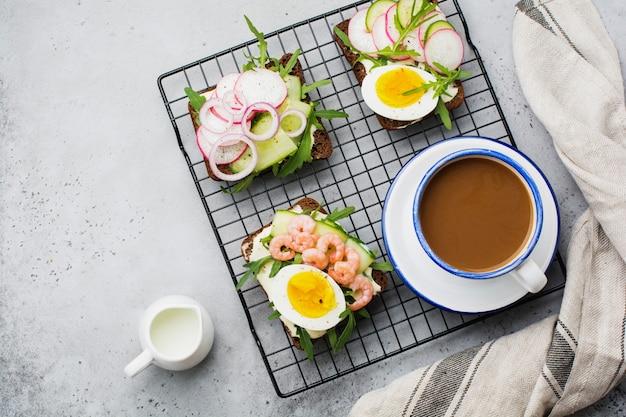 Otwarte kanapki na ciemnym chlebie żytnim z jajkiem, krewetkami, rzodkiewką, ogórkiem, twarożkiem i rukolą na śniadanie