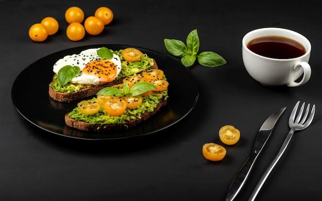 Otwarte kanapki z guacamole z awokado, żółtymi pomidorami cherry, jajkiem sadzonym i bazylią na czarnym talerzu. zdrowe jedzenie lub przekąska