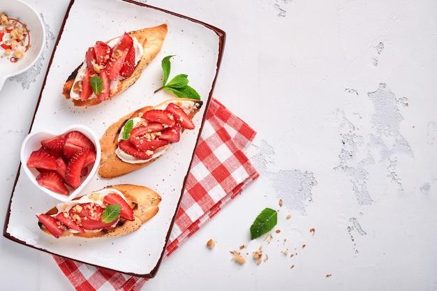 Otwarte kanapki z truskawkami, miękką miętą serową i orzechami włoskimi w ceramicznym talerzu na jasnoszarym kamiennym tle. lato i zdrowa dieta jedzenie, wegetariańska koncepcja żywności. widok z góry.