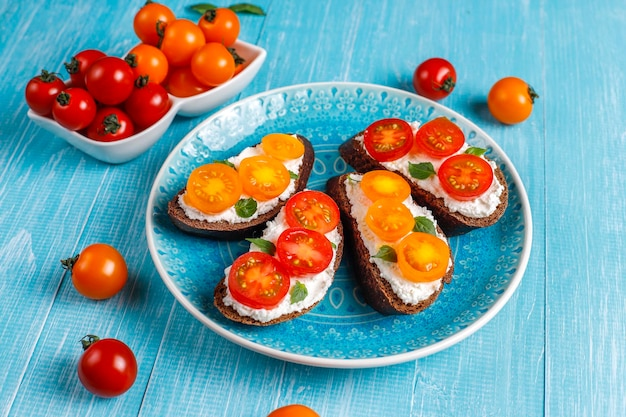 Otwarte kanapki z twarogiem, pomidorkami cherry i bazylią.