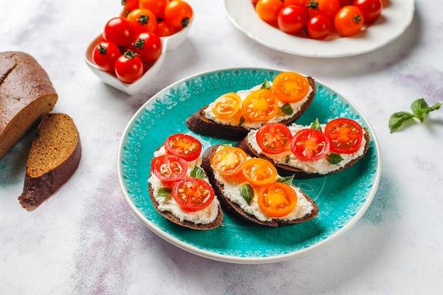 Otwarte kanapki z twarogiem, pomidorkami koktajlowymi i bazylią.