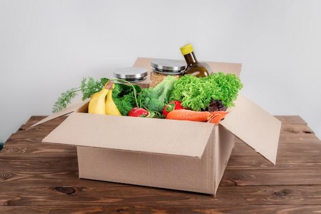 Otwarte kartonowe pudełko pełne jedzenia w domowej kuchni