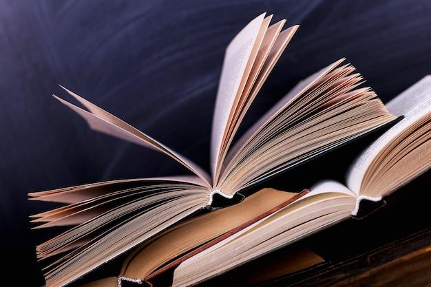 Otwarte książki to stos na biurku, na tle tablicy kredowej. trudna praca domowa w szkole, góra wiedzy.