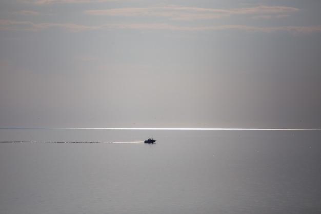 Otwarte morze. w oddali płynie łódź. niebo prawie zlewa się z wodą. szlak łodzi biegnie równolegle do horyzontu. jest miejsce na kopię.