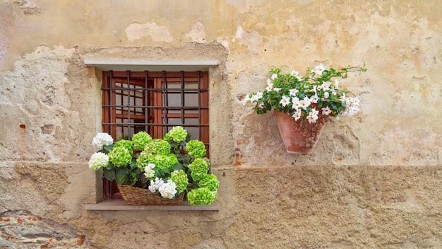Otwarte okno z kratą i kwiatami na parapecie.