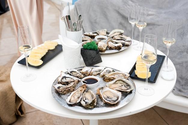 Otwarte ostrygi i cytryna z białym winem na stole.