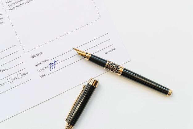 Otwarte pióro na papierze z podpisem