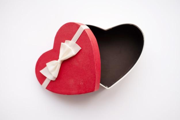 Otwarte pudełko czerwone serce z białą wstążką na białym tle