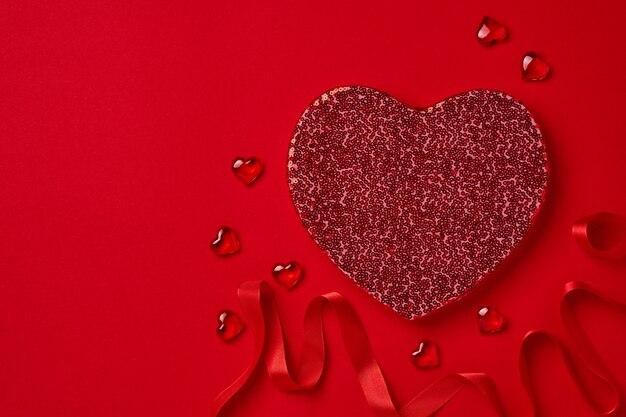 Otwarte pudełko z czerwonym sercem, wstążka i porozrzucane serca na szkarłatnym stole. walentynki pocztówka lub koncepcja. miejsce na tekst. widok z góry.
