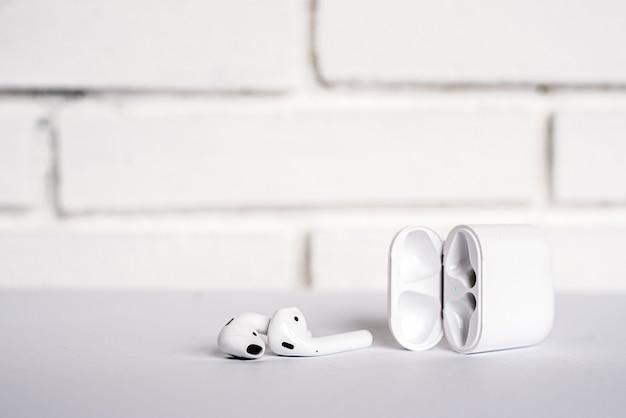 Otwarte pudełko z nowoczesnymi, prawdziwie bezprzewodowymi słuchawkami dousznymi umieszczonymi na stole przy białej ścianie z cegły