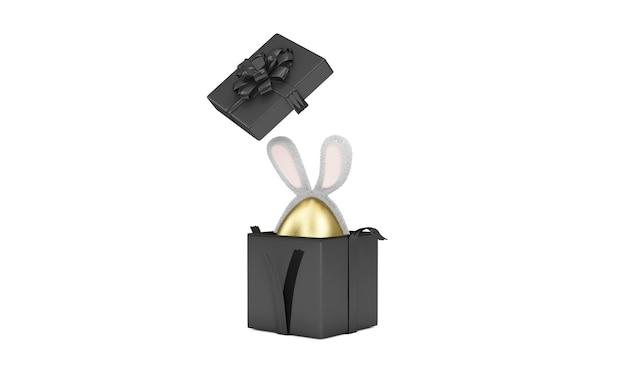 Otwarte pudełko ze złotym jajkiem wielkanocnym z uszami futrzanego królika wewnątrz na białej ścianie